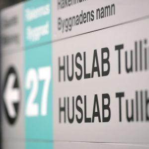 Skylt med texten HUSLAB Tullbommen.