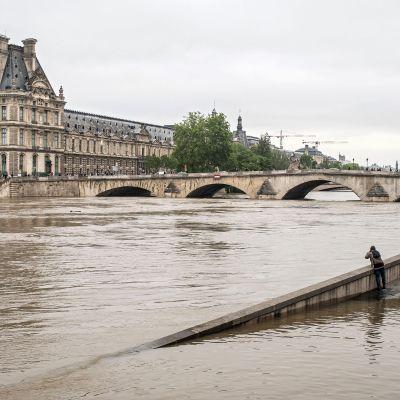 Ihmiset katsovat kohti Louvren museota puoliksi veden varaan peittyneen tien varrella Seinen rannalla.