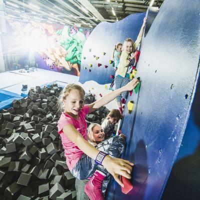 Nuoria tyttöjä kiipeilemässä SuperParkissa.