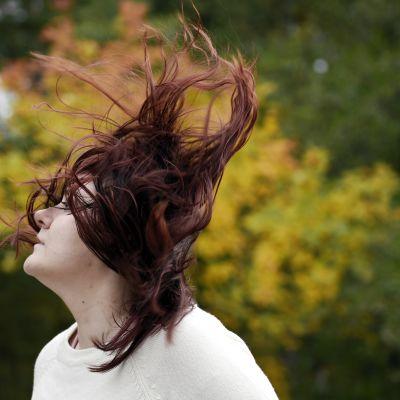 Nuori nainen seisoo hiukset hulmuten tuulessa.