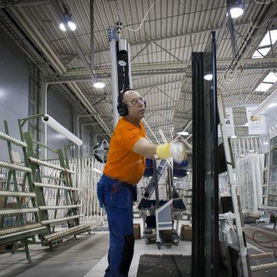 Työntekijä asentaa lasia Skaalan tehtaalla.