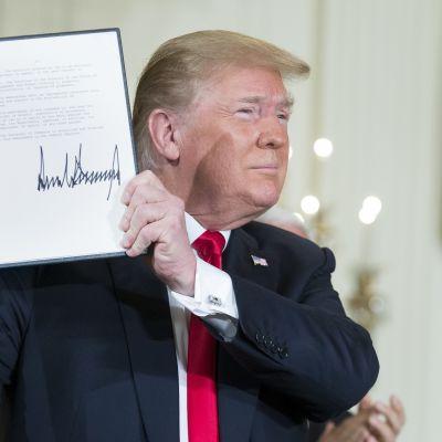 Yhdysvaltain presidentti Donald Trump pitelee käsissään allekirjoittamaansa asiakirjaa ja esittelee sitä katsojien suuntaan.