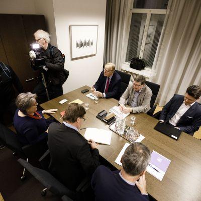 Pöydän ympärillä PAM:n entinen puheenjohtaja Ann Selin (edessä vasemmalla), valtiosihteeri Raimo Luoma sekä entinen valtakunnansovittelija Jukka Ahtela. Pöydän toisella puolella istuivat entinen SAK:n puheenjohtaja Lauri Ihalainen (vasemmalla), eläköitynyt EK:n työmarkkinajohtaja Lasse Laatunen sekä valtiosihteeri Valtteri Aaltonen (pöydän takana oikealla).