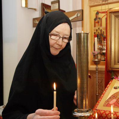 Kuvassa Lintulan luostarin nunna pitelee kynttilää kädessään mietteliään näköisenä.