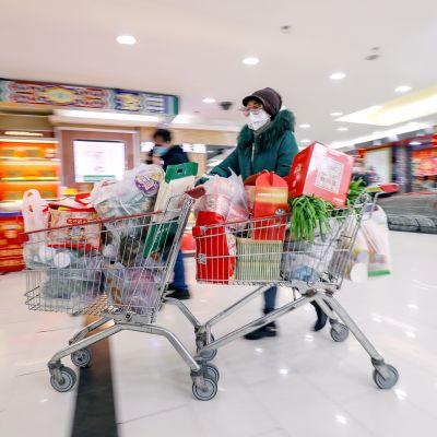 Hengityssuojaimeen pukeutunut nainen työntää täyteen lastattuja ostoskärryjä ruokakaupassa Wuhanissa.