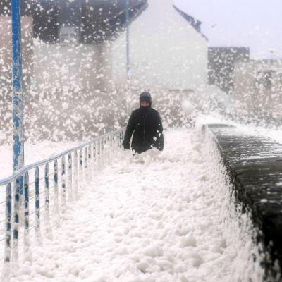 Jalankulkija kävelee vaahdossa merenrannalla Ranskassa.