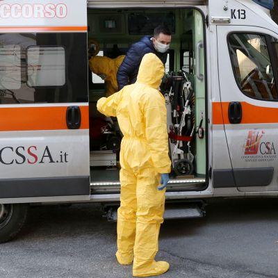 Suojapukuihin pukeutuneet terveystyöntekijät auttavat henkilöä ulos ambulanssista Italian Paduassa.