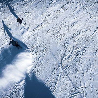 Aurinko paistaa, kun laskettelijat kiitävät alas lumen peittemää rinnettä.