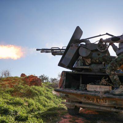 Turkkilaistaustainen syyrialainen taistelija tulittaa auton lavalta Afissa.