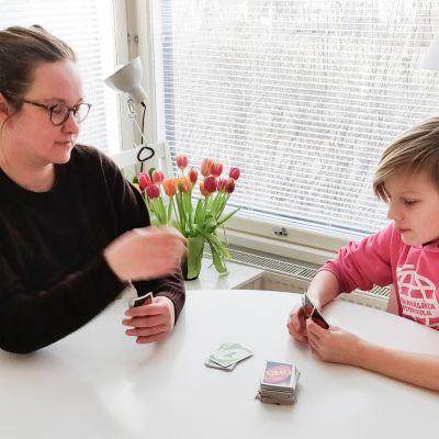 Katrianna Raunio pelaa karanteenissa olevan poikansa kanssa korttia pöydän ääressä.