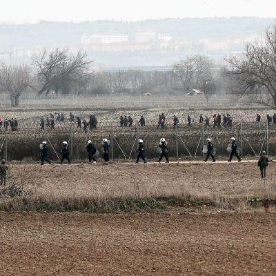 Kreikkalaiset mellakkapoliisit seuraavat siirtolaisia Turkin ja Kreikan välisellä rajalla.