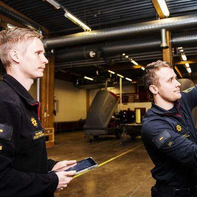 Kuvassa palomiehet Mirko Lindgren  ja Peter Moisio tekevät kuukausitarkastusta paloautolle.