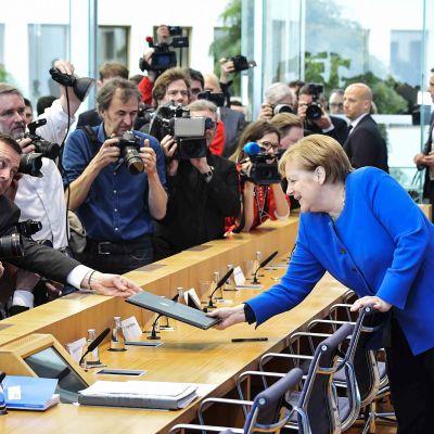 Saksan terveysministeri Jens Spahn ojentaa dokumentteja Angela Merkelille.