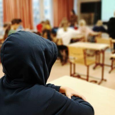 Poika istuu koululuokassa erillään muista.