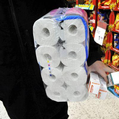 Kuvassa on henkilö kaupassa, vessapaperia mukanaan.