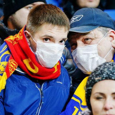Nuori ja vanha mies hengityssuojien kanssa jalkapallo-ottelussa.