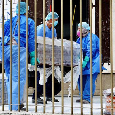 Koronavirukseen kuolleen arkkua kannetaan Guayaquilissa.