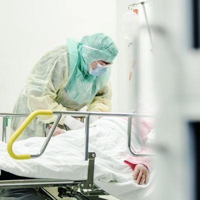 Suojavarustukseen pukeutunut hoitaja ottaa näytettä koronaepäillyltä.