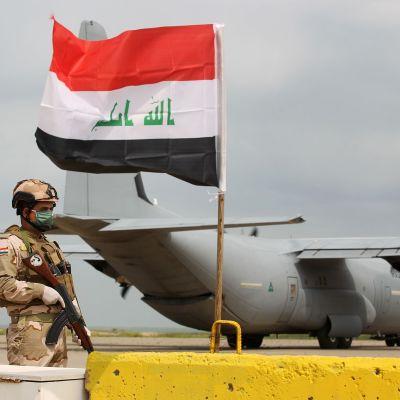 Sotilas seisoo Irakissa Yhdysvaltain lentokoneen edustalla.