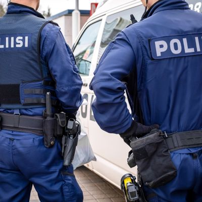 Kaksi järjestyspoliisia takaapäin kuvattuna.