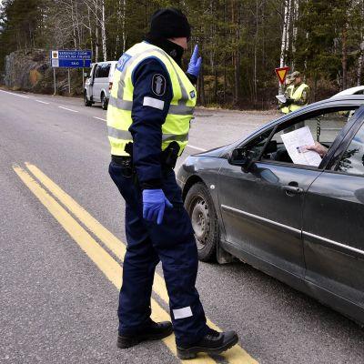 Kuvassa poliisi tarkastaa autoilijaa tiellä.