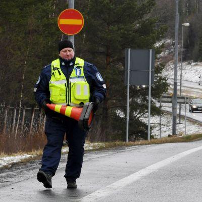 Kuvassa poliisi kävelee Uudenmaan purettavalla rajausululla.