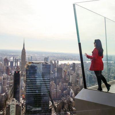 Nainen katsoo maisemaa pilvenpiirtäjän näköalatasanteella New Yorkissa.