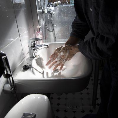 Mies pesee käsiään saippualla kylpyhuoneessa.