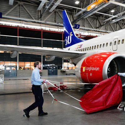 Lentomekaanikot asentavat suojia lentokoneen moottorin päälle lentokoneiden säilytyshallissa Oslossa.
