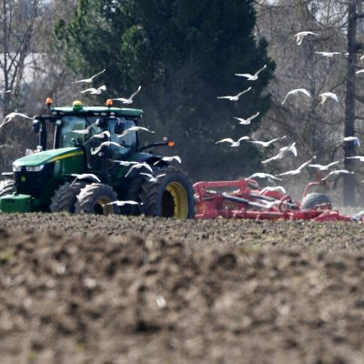 Kuvassa traktori äestää pellolla.