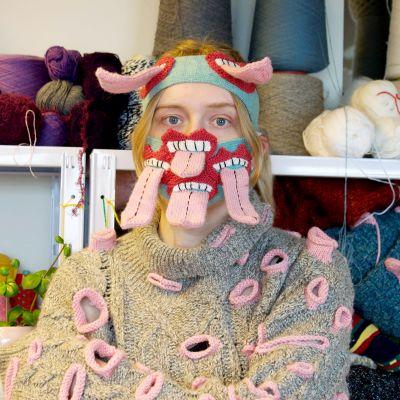 Islantilainen muotisuunnittelija poseeraa taiteellinen maski kasvojensa suojana.