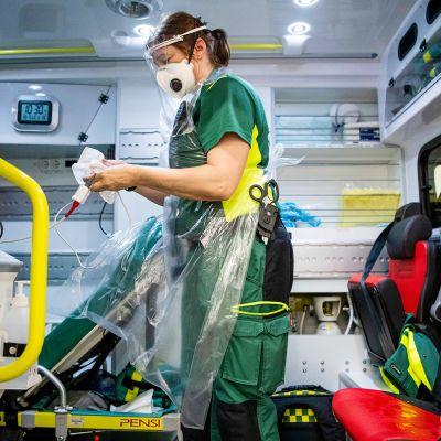 Ensihoitaja desinfioi ambulanssia Tukholmassa.
