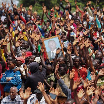 Kuvassa kannattajat pitelevät Burundissa presidenttiehdokas Agathon Rwasan kuvaa.