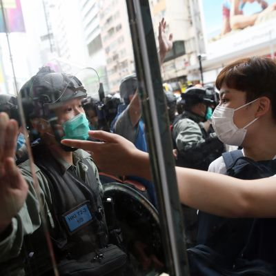 Mellakkapoliisi ja mielenosoittajat kohtaavat Hongkongissa.