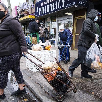 Kuvassa on newyorkilaisia noutamassa ruokakasseja.