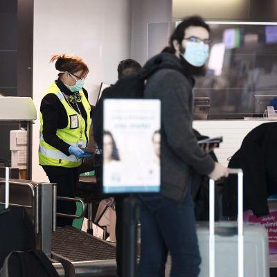 Matkustajia ja henkilökuntaa Helsinki-Vantaan lentoaseman palvelutiskillä Vantaalla.