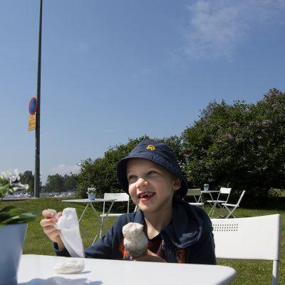 Lapsi syö jäätelöä Sibeliuspuiston jäätelökioskilla.