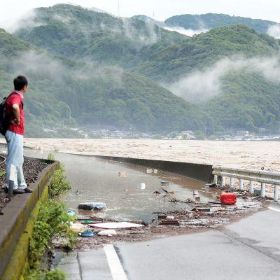 Mies katsoo tielle tulvinutta jokea Japanin Yatsushirossa