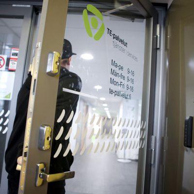 Mies astuu sisään työvoimatoimiston ovesta.