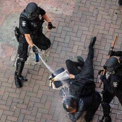 Poliisi suihkuttaa mielenosoittajia.