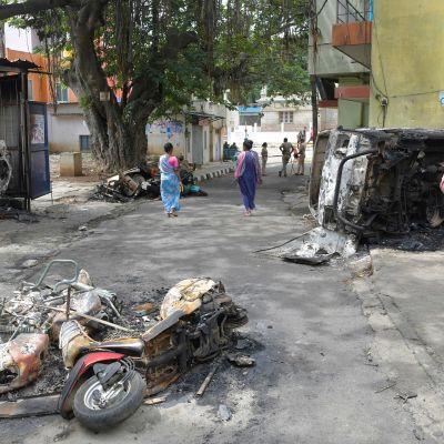 Mellakoissa tuhoutuneita ajoneuvoja kadulla Bengalurussa.
