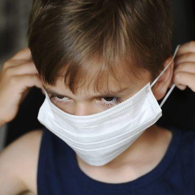 Kuvassa on hengityssuojainta käyttävä lapsi.