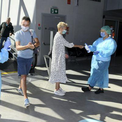 Hoitohenkilöstöä ja laivamatkustajia terveysneuvontapisteessä Länsiterminaalissa Helsingissä 17. elokuuta 2020.