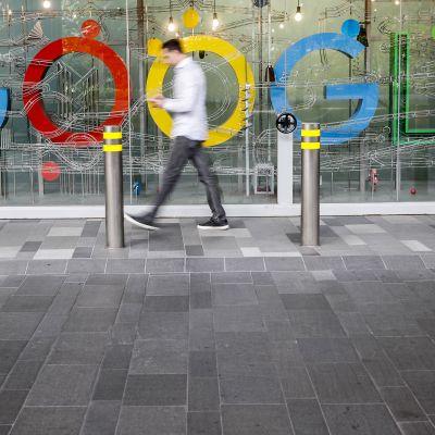 Mies käyttää matkapuhelinta googlen logon edustalla Singaporessa.