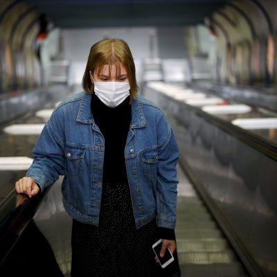 Hengityssuojainta käyttävä nainen Ruoholahden metroasemalla Helsingissä 4. elokuuta 2020.
