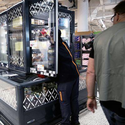 Kaupan työntekijä ja asiakas ruokakaupassa.