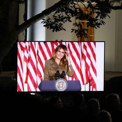 Melania Trump kuvattuna Valkoisen talon puutarhassa sijaitsevan näytön ruudulta..