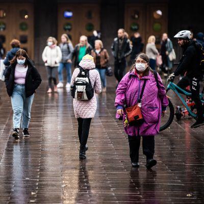 Kasvomaskeihin pukeutuneita ihmisiä Helsingin rautatieaseman edustalla.