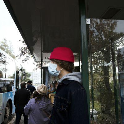 Kasvomaskiin pukeutunut nuori bussipysäkillä.