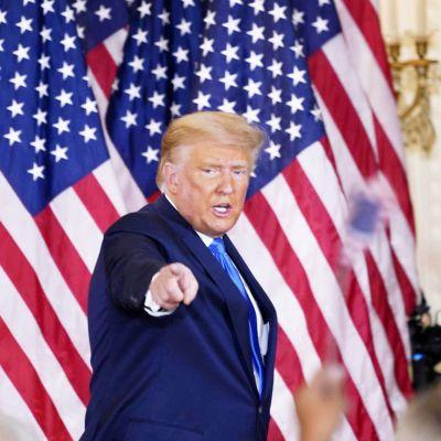 Yhdysvaltain presidentti Donald Trump osoittaa kameraa, taustalla Yhdysvaltain lippuja
